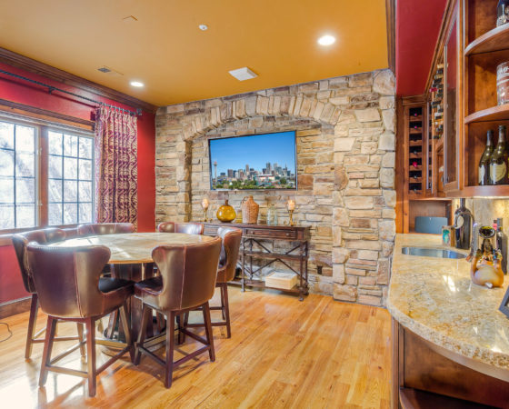 Wine Room with rich red wall accents and custom table by My Inside Designer