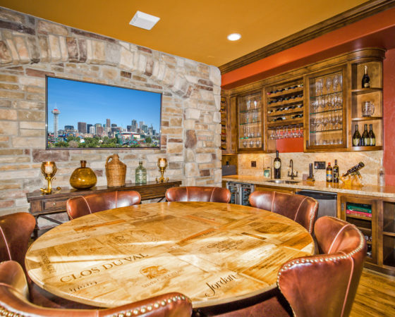 Redecorated Wine Room in Castle Pines CO with rich color wall treatments and custom wine-crate table top by My Inside Designer