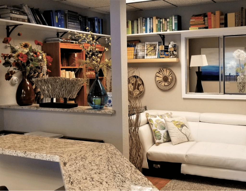 White sofa with print pillows, shelves with books, blue glass vase on shelf with dried flowers